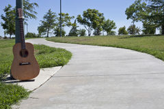 Calzada del cemento con la guitarra que se reclina contra un Ligh Fotografía de archivo