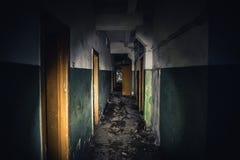 Calzada en el edificio abandonado espeluznante, pasillo asustadizo oscuro con muchas puertas, concepto del fondo del horror fotos de archivo