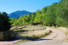 Calzada larga con la vista de montañas y de árboles fotos de archivo