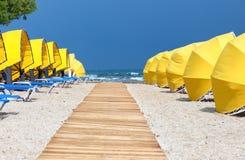 Calzada, paraguas y sunbeds de madera Fotos de archivo
