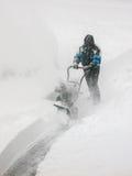 Calzada que sopla de la nieve del hombre en ventisca Fotos de archivo libres de regalías