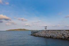 Calzada rocosa que lleva al océano con el pequeño fondo de la isla, Fotografía de archivo