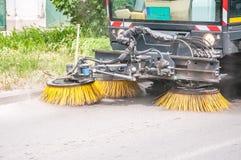 Calzada y camino con agua y limpieza que se lavan del vehículo del barrendero de calle con los cepillos giratorios del vacío, con Fotografía de archivo libre de regalías
