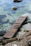 Calzadas de madera en la costa guijarrosa imagen de archivo