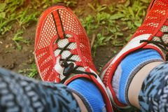 Calzado en los pies Zapatillas de deporte rojas imagenes de archivo