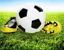 Calzado y balón de fútbol en hierba Fotos de archivo libres de regalías