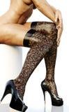Calze d'uso della donna adatta sulle gambe sexy lunghe che mostrano la sua parte, posante su un fondo bianco isolato Immagini Stock