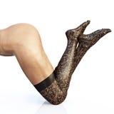 Calze d'uso della donna adatta sulle gambe sexy lunghe, vista laterale sulle sue ginocchia isolate su fondo bianco Immagine Stock