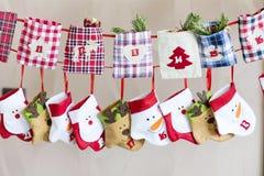 Calze di Natale per i regali - appendendo su una corda rossa Fotografia Stock