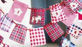 Calze di Natale per i regali che appendono sulla corda rossa Fotografie Stock Libere da Diritti