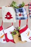 Calze di Natale per i regali che appendono sulla corda rossa - alto vicino Immagini Stock Libere da Diritti