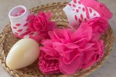 Calzini del bambino, fiore rosa, uovo giallo in un piatto di vimini su una tavola Fotografie Stock Libere da Diritti