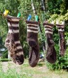 Calzini della lana che appendono sulla corda da bucato Fotografia Stock