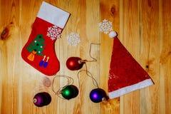 Calzini di Natale e cappello di Santa con i fiocchi di neve delle palle Fotografia Stock