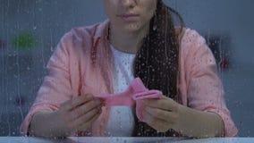 Calzini rosa minuscoli di tenuta femminili deprimenti, vittima ostetrica di violenza, aborto stock footage