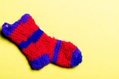 Calzino di lana tricottato di colore rosso con le bande blu su un fondo giallo Immagini Stock