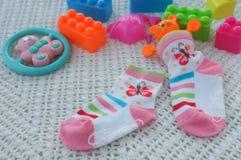 Calzino e giocattolo per il bambino su una morbidezza Immagine Stock