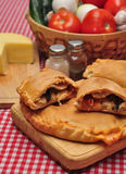 Calzone. Sliced in two, on top of others, on a table with fresh ingredientes and checkered tablecloth Royalty Free Stock Image