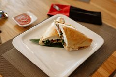 Calzone pizza halves on bamboo sheet in square plate on wooden table royalty free stock images