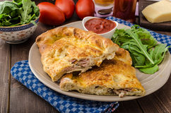 Calzone pizza som är välfylld med ost och prosciuttoen Royaltyfria Foton