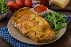 Calzone pizza stuffed with cheese and prosciutto Royalty Free Stock Images