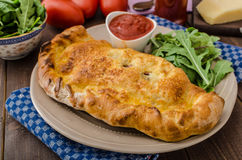 Calzone pizza stuffed with cheese and prosciutto Stock Image