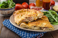 Calzone pizza stuffed with cheese and prosciutto Stock Photography