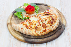 Calzone pizza on wooden dish Stock Photo