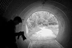 Caméra asiatique de participation d'homme se penchant dans le tunnel photographie stock libre de droits