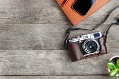 Caméra classique avec un stylo rouge d'organisateur brun sur un bureau gris en bois, de cru avec un téléphone et une croissance v images stock