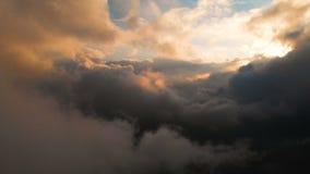Caméra d'envergure par les nuages de pluie égalisants au coucher du soleil au-dessus des niveaux de nuage Vol fabuleux dans les n banque de vidéos