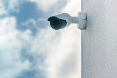 Caméra de sécurité de télévision en circuit fermé à l'arrière-plan avant de ciel bleu installé sur le mur de construction blanc image stock
