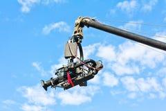 Caméra de télévision sur une grue contre le ciel bleu Photographie stock