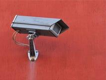 Caméra grise de rue de surveillance externe sur un mur de construction coloré par terre cuite images libres de droits