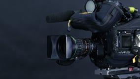 Caméra vidéo numérique professionnelle, camcoder d'isolement sur le fond noir dans le srudio de TV banque de vidéos