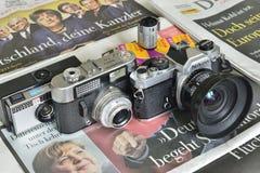 Caméras analogues sur des journaux images stock