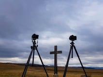 Caméras D800 et D300 de Nikon sur des trépieds de Manfrotto devant la croix en bois photo libre de droits
