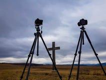 Caméras D800 et D300 de Nikon sur des trépieds de Manfrotto devant la croix en bois photos libres de droits