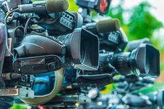 Caméras de télévision professionnelles sur des trépieds enregistrant l'événement social photographie stock libre de droits