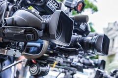Caméras de télévision professionnelles sur des trépieds enregistrant l'événement social images libres de droits