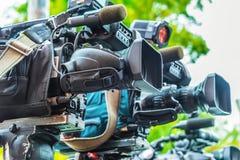 Caméras de télévision professionnelles sur des trépieds enregistrant l'événement social photographie stock
