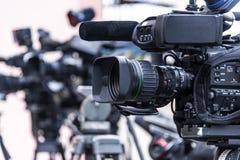 Caméras de télévision professionnelles sur des trépieds enregistrant l'événement social images stock