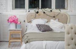 Cama acogedora blanca con la almohada del vintage y las luces de la Navidad Fotografía de archivo