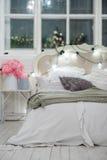 Cama acogedora blanca con la almohada y las luces de la Navidad, defocus del vintage Foto de archivo