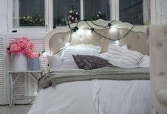 Cama acogedora blanca con la almohada y las luces de la Navidad, defocus del vintage Imagenes de archivo