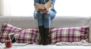 Cama acogedora blanca y una muchacha hermosa con un ordenador y un libro, bebiendo una bebida caliente Imagenes de archivo
