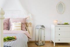Cama, aparador y linterna decorativa imagen de archivo