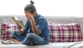 Cama cómoda y muchacha que leen un libro Fotos de archivo