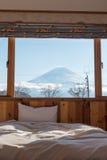 Cama con la TA Opinión de Fuji como fondo fuera de la ventana Imágenes de archivo libres de regalías