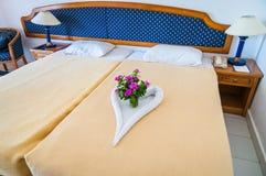 A cama da lua do mel com coração de toalha deu forma na cama Fotografia de Stock